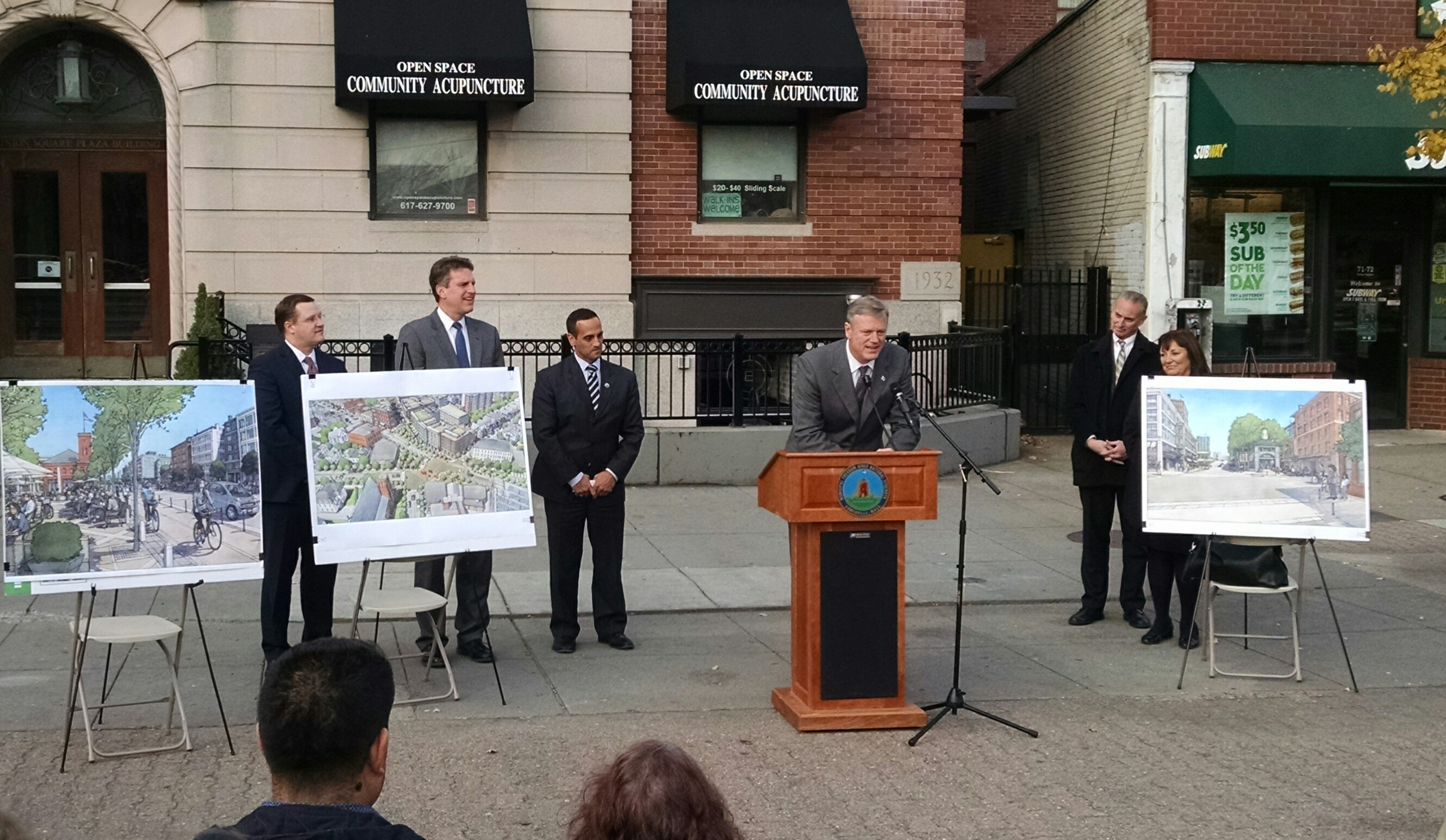 Massachusetts Governor Charlie Baker stands at a podium with Mayor Joseph Curtatone to display renderings of the future of Union Square infrastructure