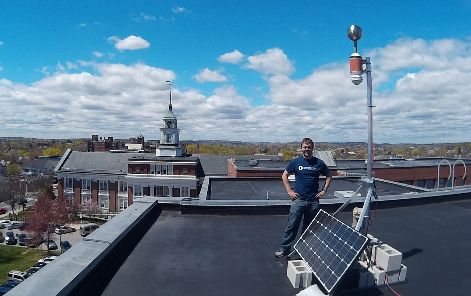 An Understory Weather team member stands in front a solar array hooked to a weather monitoring system on the roof of Somerville High School.