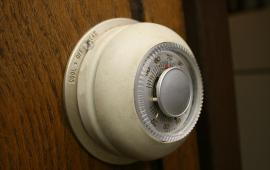 An analog dial thermostat in a home set to 68F