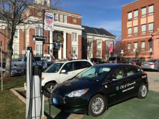 An electric vehicle sits at one of the EV charging stations in from of Somerville City Hall