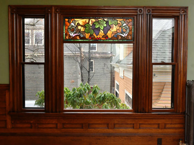 Restored stained glass window at 83 Belmont St. with grapevine pattern