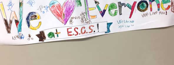 "A child-drawn poster pronounces ""we love everyone at ESCS"""