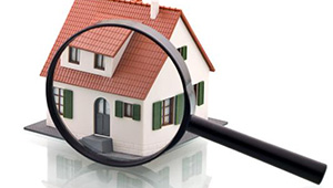 Cartoonish image of a giant magnifying glass inspecting a house