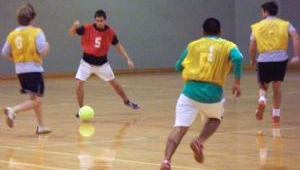 Children play indoor soccer on a gymnasium floor