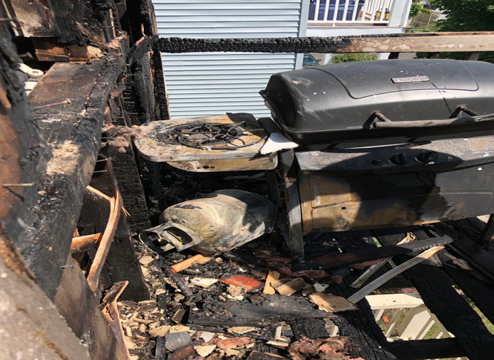 A charred porch illustrates the danger of using a grill on a balcony, which is prohibited in Somerville.