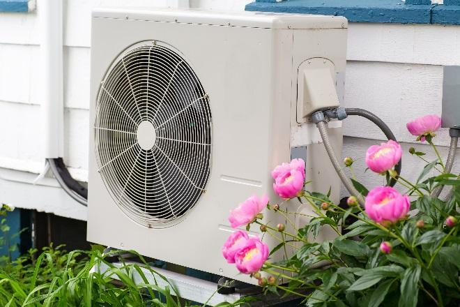 A typical heat pump, consisting of a boxy white frame similar to an air conditioning unit, is pictured on the side of a home.
