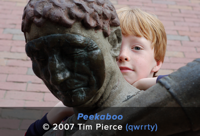 Boy plays peekaboo behind a statue