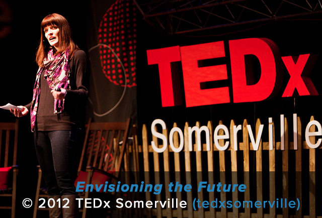 A woman holding a microphone delivers a TEDx Somerville talk