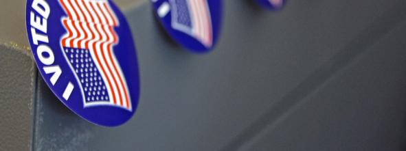 A row of 'I Voted' stickers affixed to the corner of a voting machine