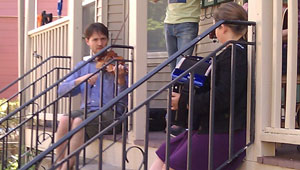 Two City residents play an accordion and a fiddle on a porch during PorchFest 2012