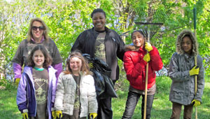 Four Somerville volunteers smile for the camera at the 2013 Spring Cleanup Event.