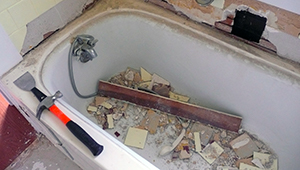 Debris and tools fill an antique bathtub during a renovation
