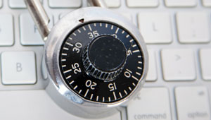 A padlock sits on top of a modern computer keyboard