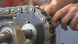 Technician adjusts the tension of a chain in a machine