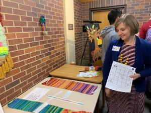SHS student stands next to her crochet project, showing colorful temperature changes over time
