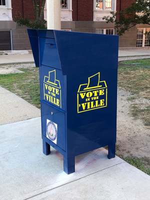 "A blue, metal ballot box with a lock, ballot slot, and yellow ""Vote in the 'Ville"" lettering in front of City Hall"