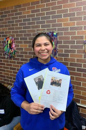 Smiling SHS student holds up outreach material