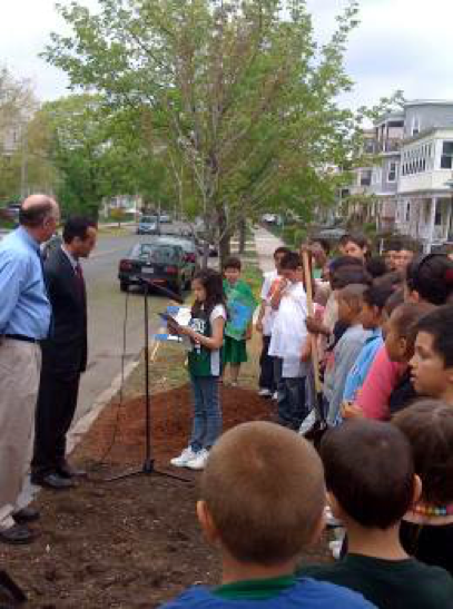 Mayor Curtatone presides over the dedication of an urban forest planting in Somerville,, and watches a child read a dedication .